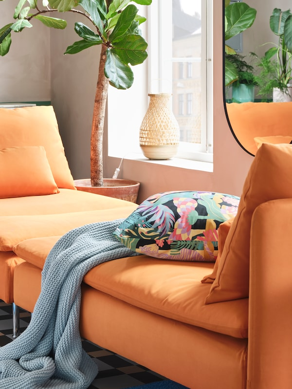 Two orange chaise longues pushed together to create a day-bed, with a blue throw and a colourful floral cushion on top.