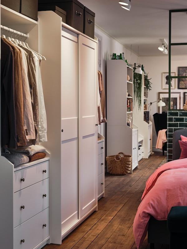 Naas een bed staat een witte HAUGA kledingkastcombinatie, en een beetje verder in de kamer een HAUGA tv-/opbergcombinatie.
