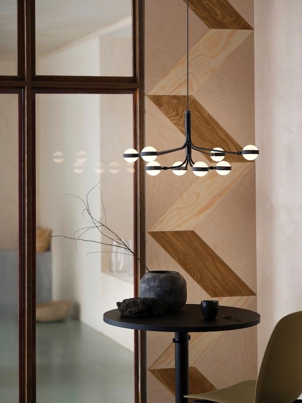 Ośmioramienny czarny żyrandol LED STORSLINGA wisi nad małym okrągłym stolikiem z ceramiką.