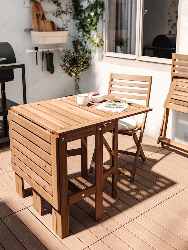 O masă de lemn pliată pe o parte pentru a economisi spațiu, cu un castron cu iaurt și fructe de pădure, o ceașcă de cafea și o revistă deasupra.