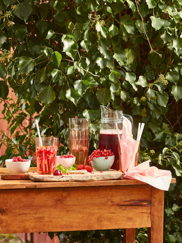 Wooden garden table with various red berries, both in filled KEJSERLIG bowls and garnishing drinks in POKAL glasses.