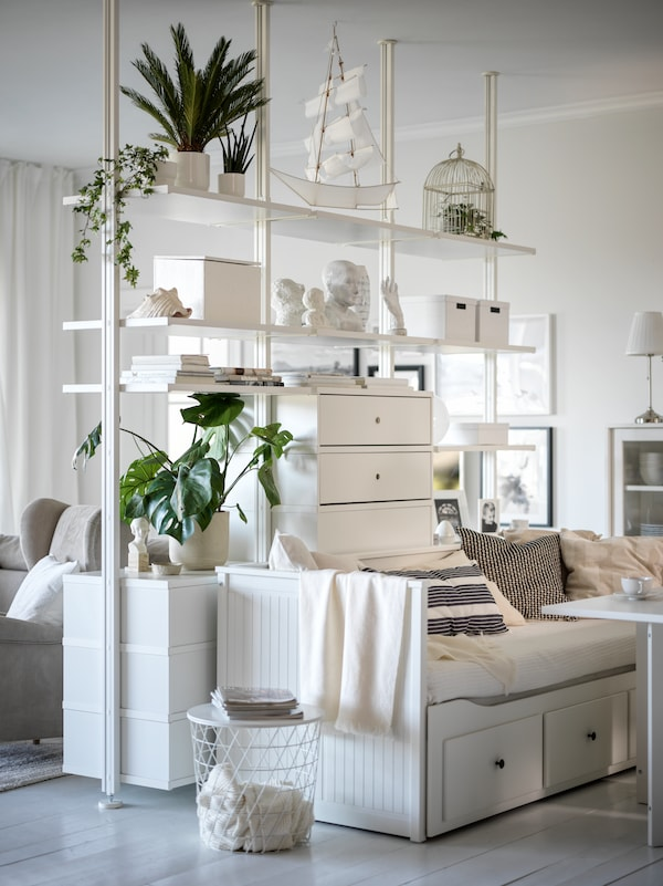 A living room with a room-dividing, floor-to-ceiling, white ELVARLI storage unit with a white HEMNES day-bed along its side.