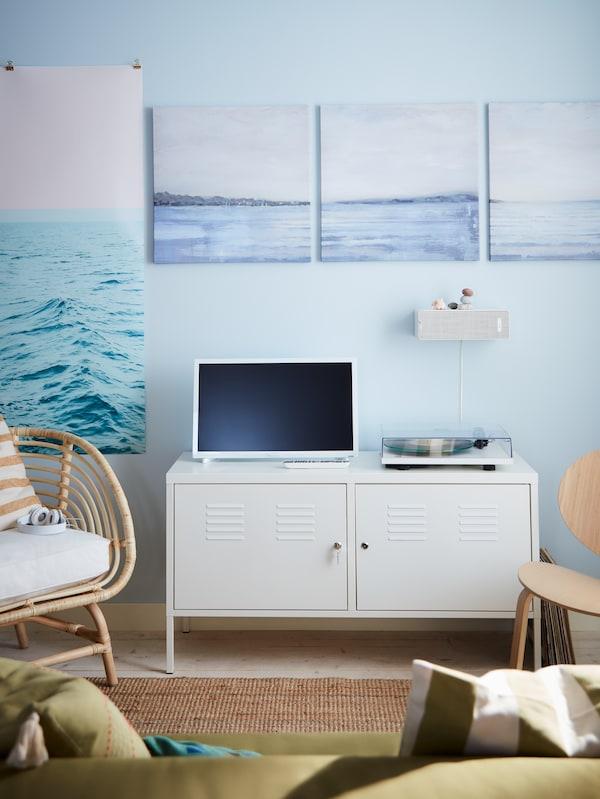 Hvidt skab ved en blå væg med billeder af havet. På skabet står et tv og en pladespiller.