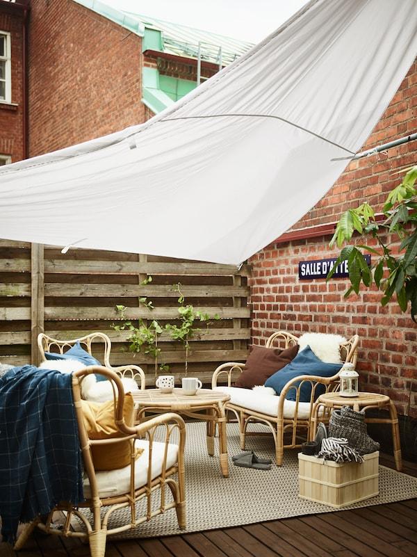 Två par umgås utomhus på kvällen i en GUNNÖN paviljong med RUNNEN trall och solcellsdrivna LED-lampor.