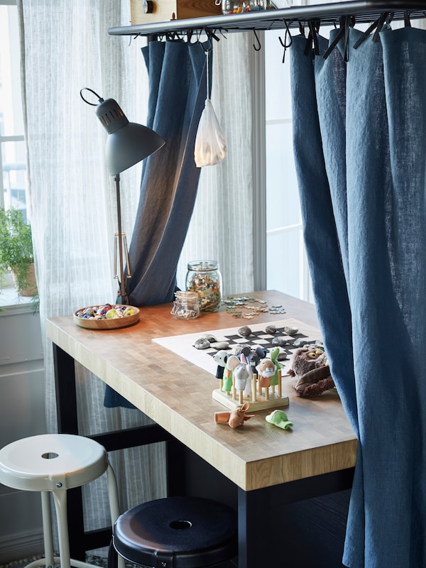 An island used as a desk with a blue/gray work lamp, blue curtains and a board game on top. Two stools are in front.