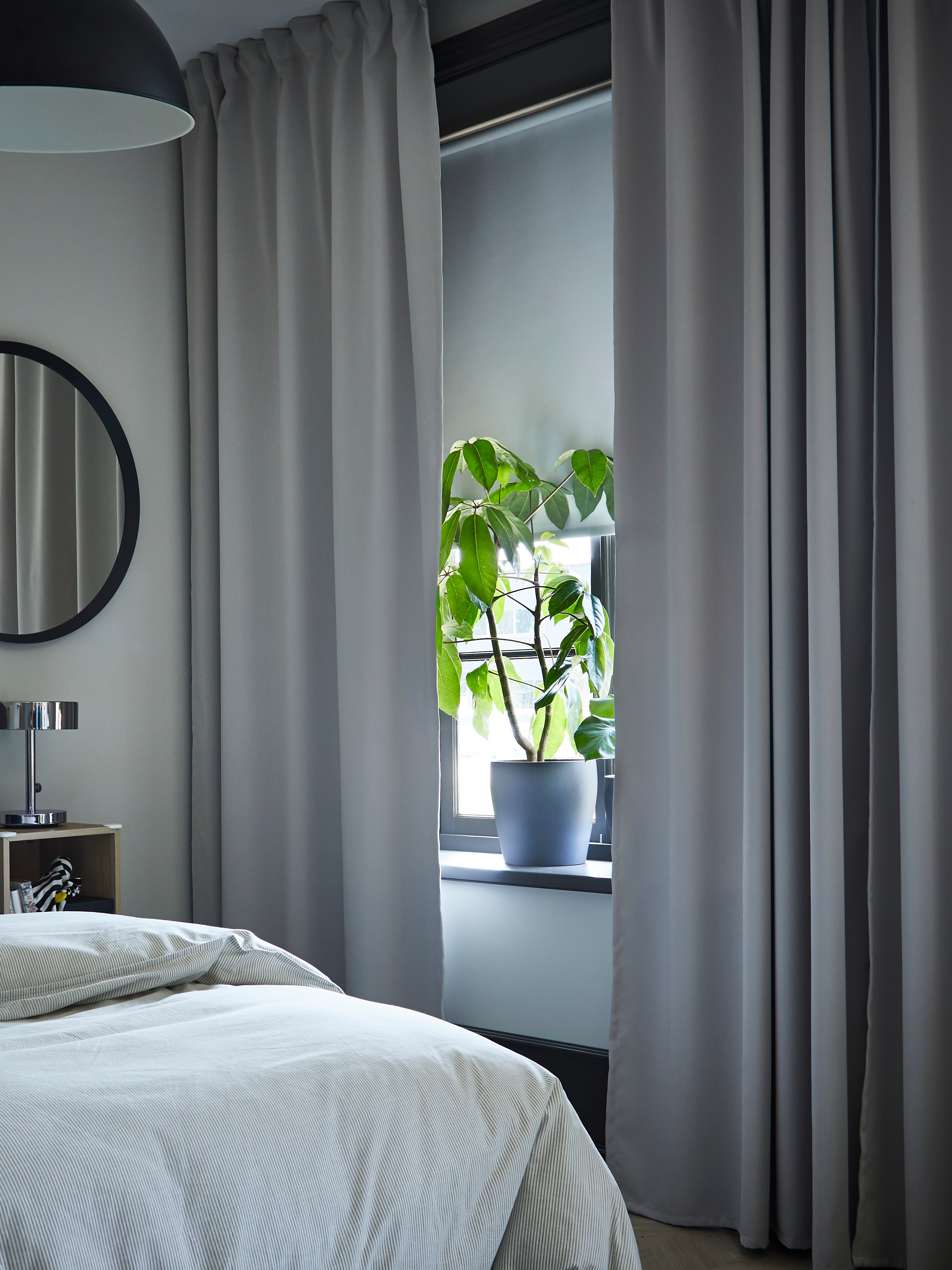 A bedroom window with light grey MAJGULL room darkening curtains and a white block-out roller blind covering half the window.
