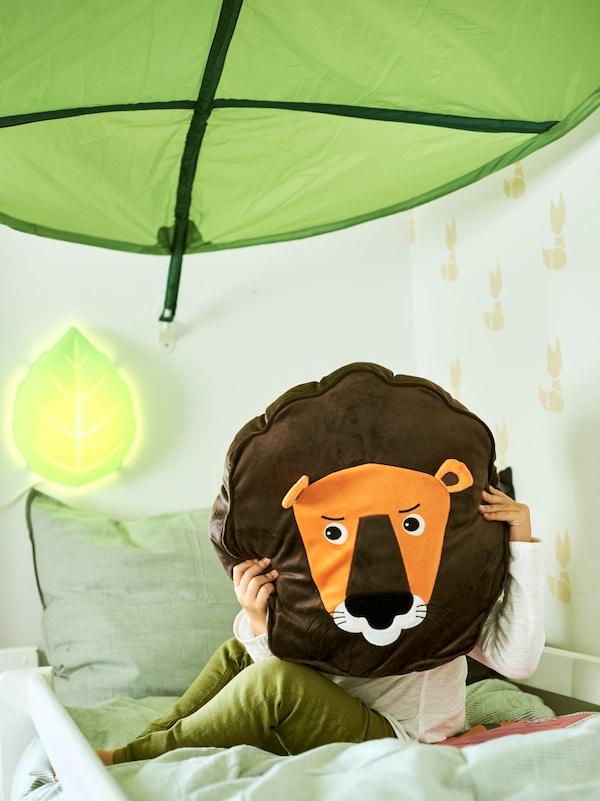 Un enfant assis sur un lit sous un ciel de lit LÖVA vert, tenant un coussin lion DJUNGELSKOG devant son visage.