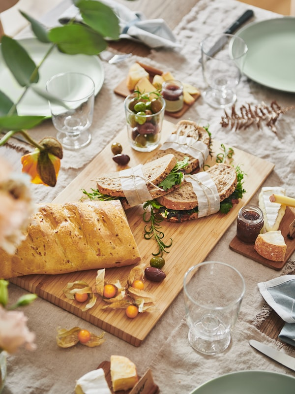 A decorated table with assorted finger food on an APTITLIG bamboo chopping board, surrounded by matt-green FÄRGKLAR plates.