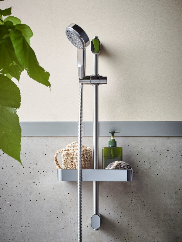 BROGRUND förkromad dusch mot en beige/beige-gråspräcklig vägg, med en tvålpump och bladen på en grön växt.