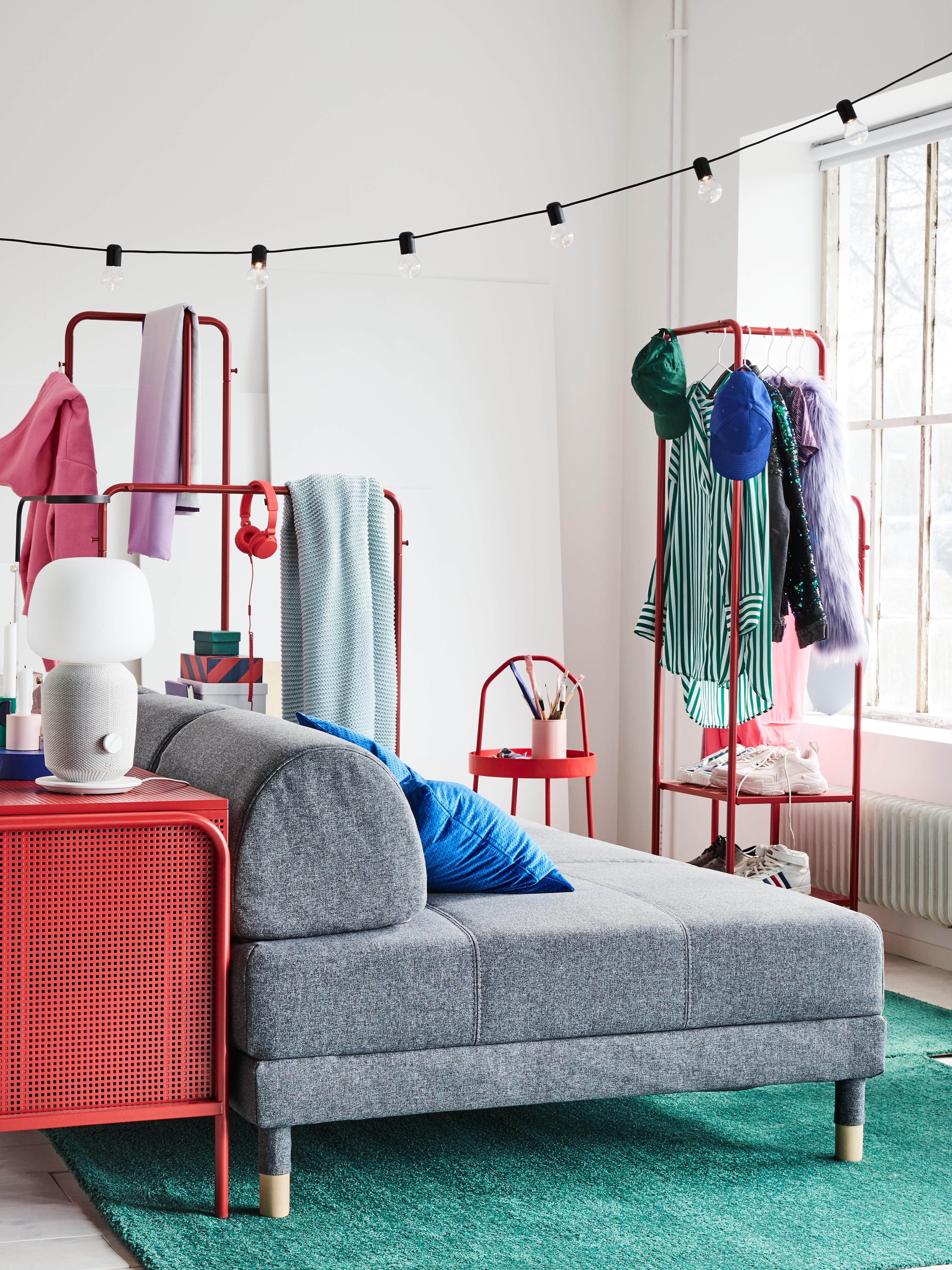 Šareni studio apartman s modernom, sivom FLOTTEBO sofom spremnom za sjedenje, zelenim tepisima i crvenom komodom.