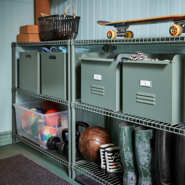 Two metal OMAR shelving units store different boxes, including metal REJSA boxes, a skateboard and sports equipment.