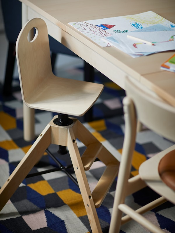Une chaise junior GRÅVAL en bouleau à côté d'une table RÖNNINGE en bouleau sur laquelle est posé un dessin d'enfant, le tout installé sur un tapis TÅRBÄK.
