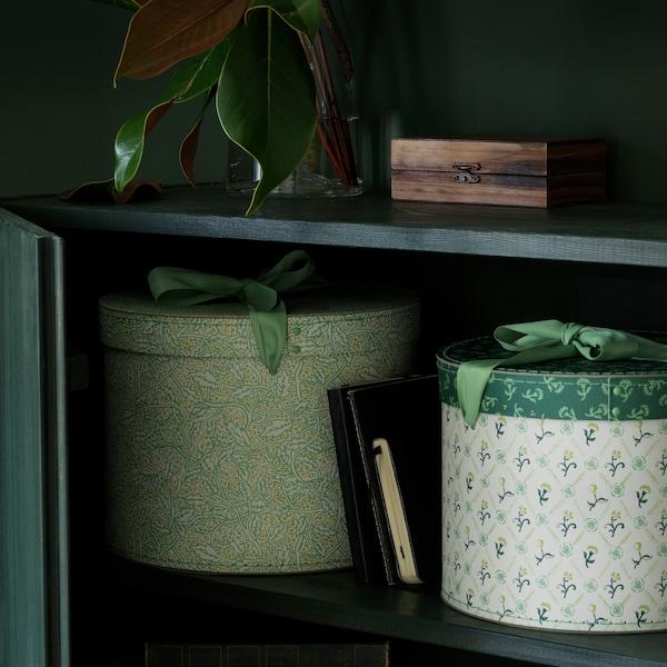 木质橱柜的下层放着两个绿色和白色储物盒,上层则放着一棵绿色植物和一个盒子。