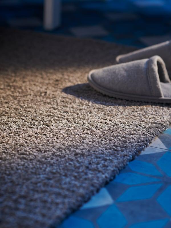 Ett par grå tofflor på en delvis solbelyst, ljusgrå LANGSTED matta står på ett blåvitt mönstrat klinkergolv.