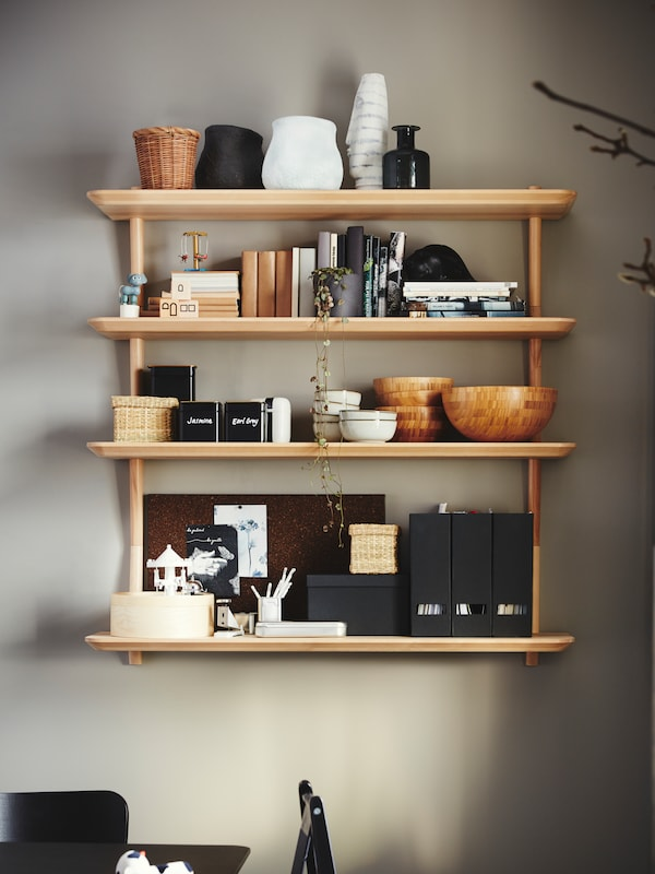 A wooden LILLABO shelving unit with 4 shelves attached to a wall holding bowls, vases, books and other objects.