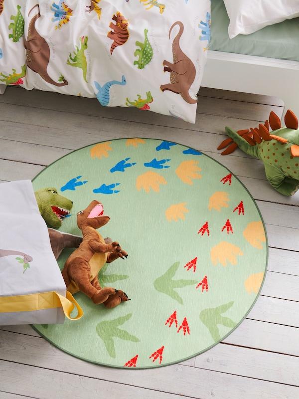 I ett barnrum ligger dinosauriemjukdjur på JÄTTELIK mattan som har ett mönster med dinosauriefotspår.