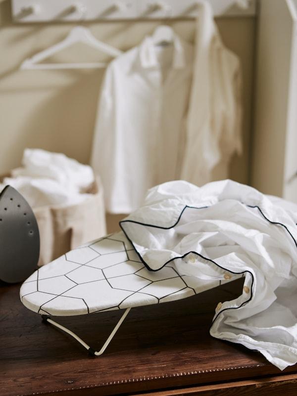 Weisse Hemden auf Kleiderbügeln, eine Holzoberfläche, ein Bügeleisen und ein JÄLL Bügelbrett, Tisch mit einem Bezug in Weiss und Schwarz.