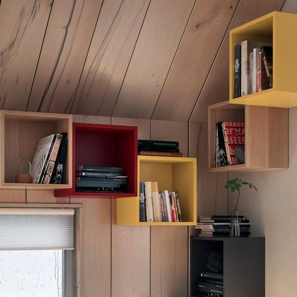Parte de um quarto com teto inclinado e em cujas paredes estão montadas estantes EKET em diferentes cores.