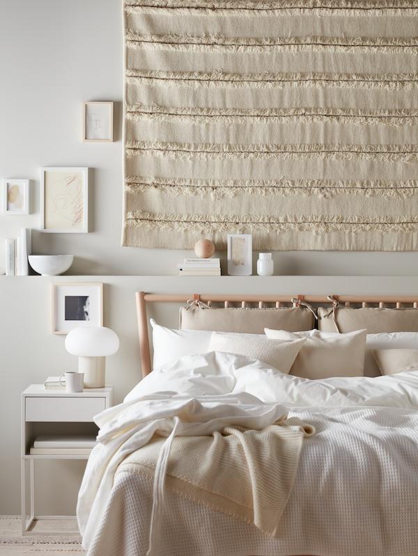 Egy hálószobában járunk, ahol egy bézs faliszőnyeget, egy ÄNGSLILJA ágyneművel kiegészített nyír BJÖRKSNÄS ágyat, mellette pedig fehér VIKHAMMER éjjeliszekrényt látunk.