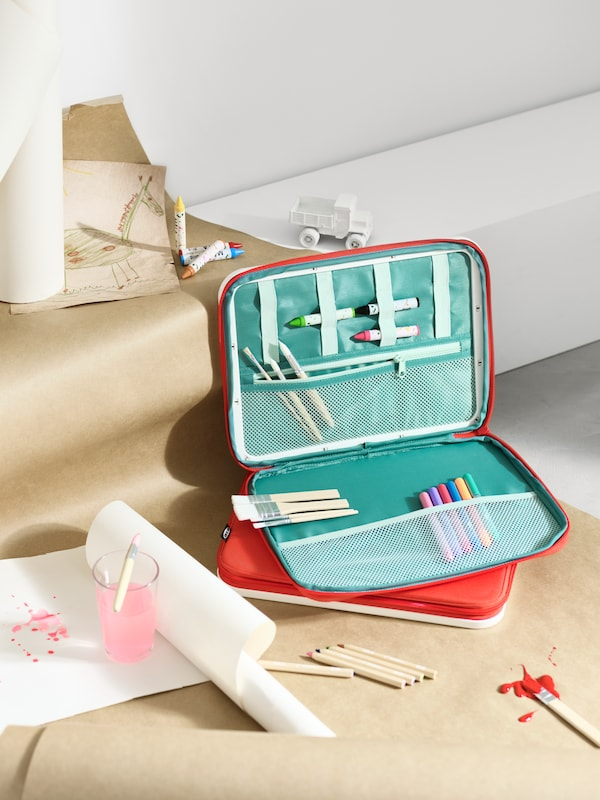 Papierrollen und eine offene MÅLA Zeichnertasche mit Malutensilien und Kinderspielzeug liegen auf einer weiteren, geschlossenen Tasche.