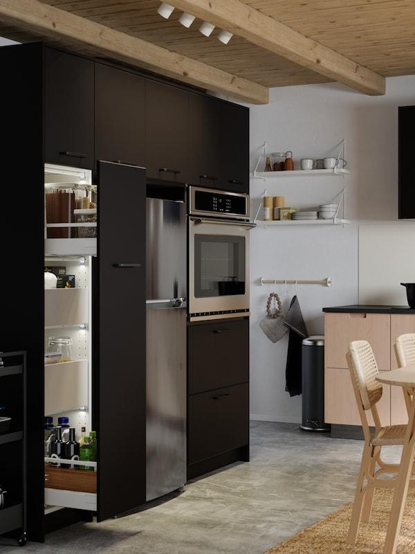 Un réfrigérateur et un four dans une cuisine avec des armoires sombres