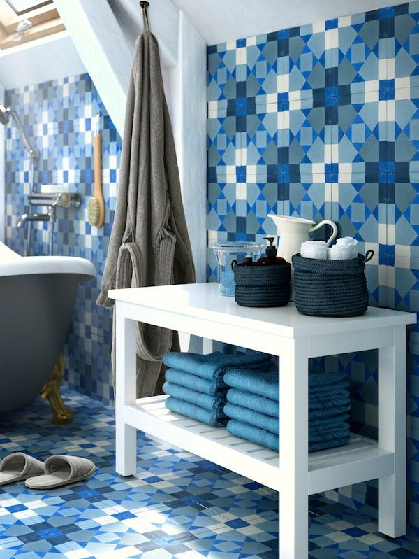 Eine weiße HEMNES Bank mit Handtüchern auf der unteren Ablage; oben drauf stehen Körbe mit Accessoiress; Fußboden und Wand sind blau-weiß gefliest.