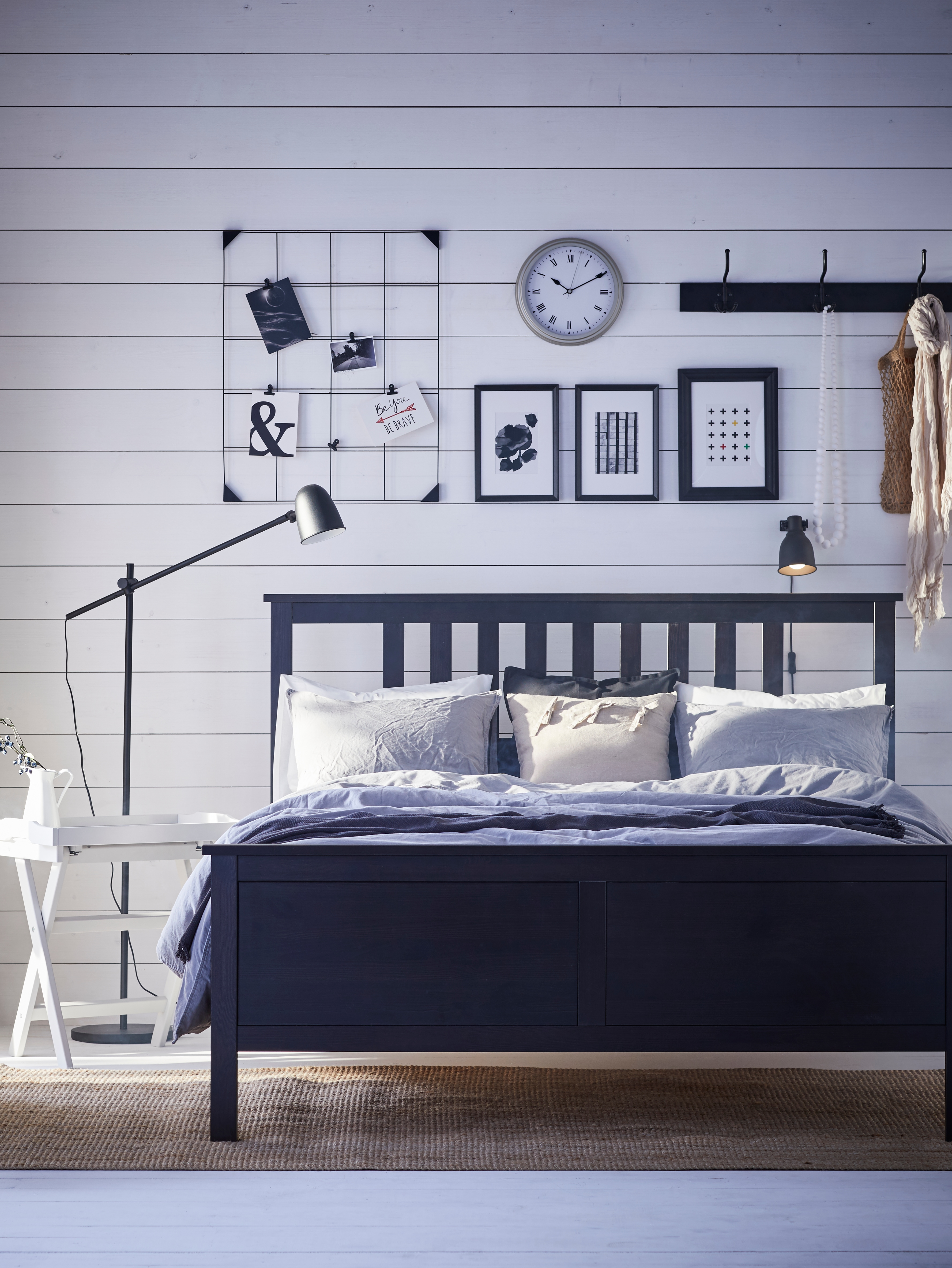 Bedroom with black bedframe, white tray table, black floor lamp, quilt cover and pillowcases, wall clock, rack with hooks.