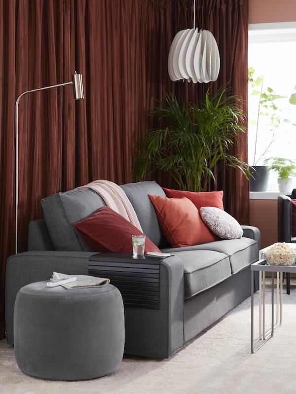 En 3-pers. sofa, lysdæmpende gardiner, en gulv-/læselampe, puder, popcorn og potteplanter.