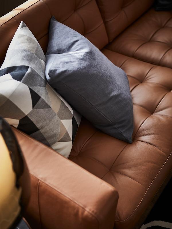 Ein IKEA LANDSKRONA Ledersofa in Braun mit zwei Kissen.