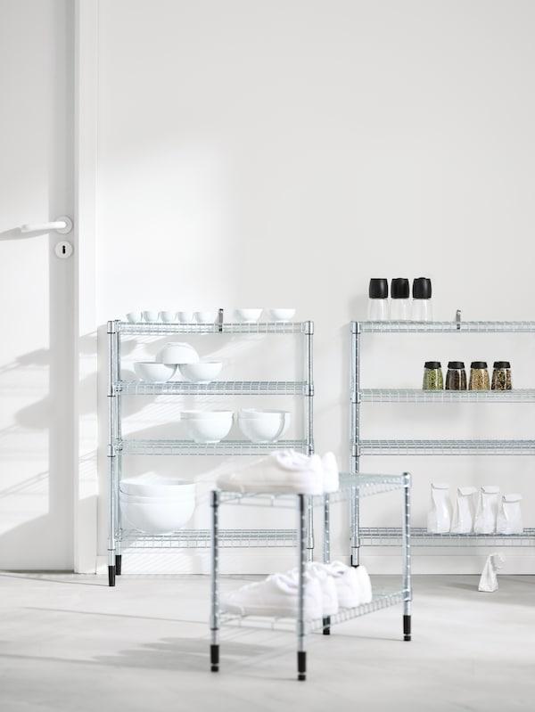 Tři policové díly OMAR s různou výškou u bílé stěny, na jednom jsou misky, na dalším sklenice a na třetím bílé tenisky.