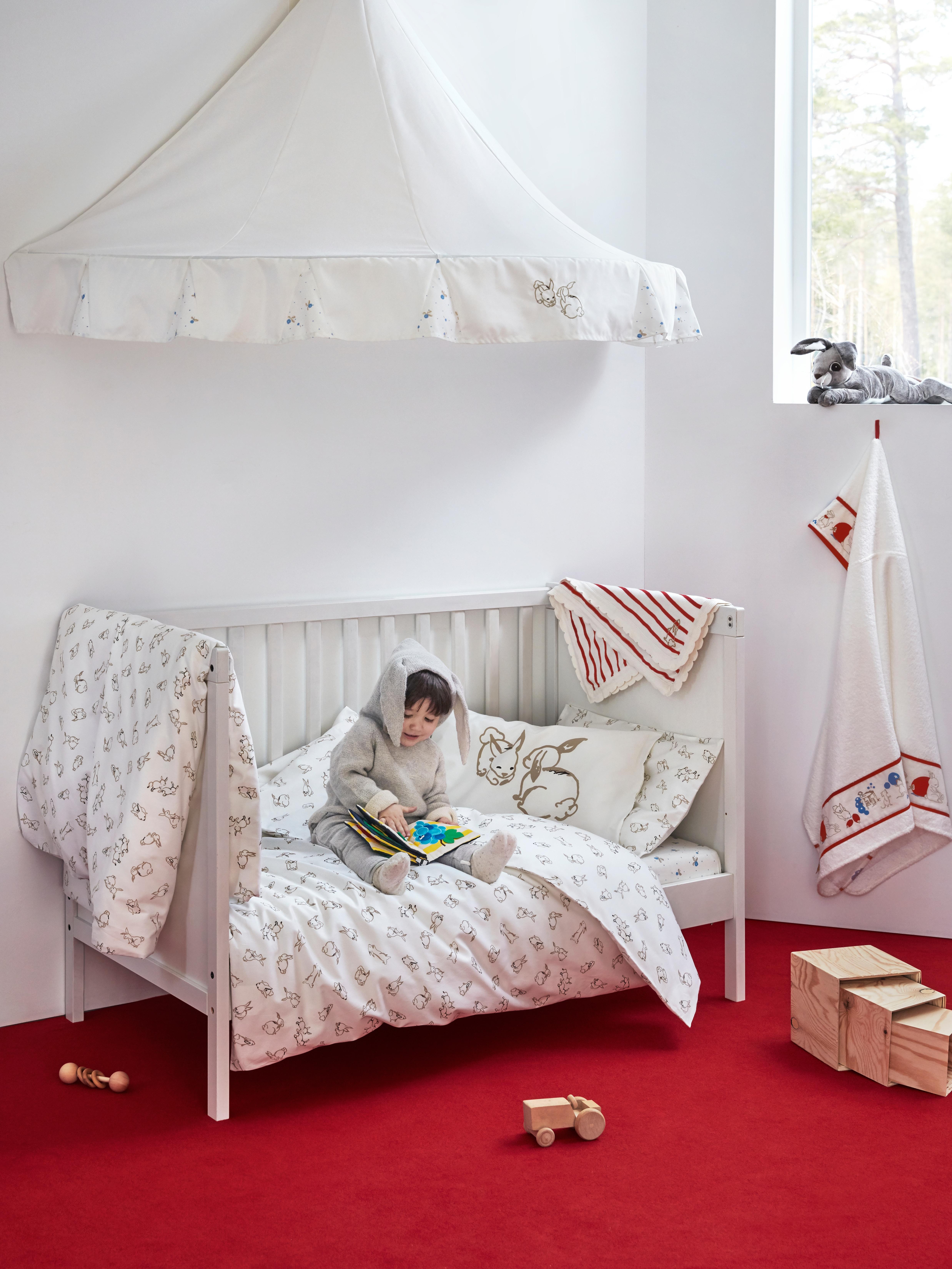 Un bambino con costume da coniglietto, seduto su una coperta in un lettino SUNDVIK bianco, in una stanza con pareti bianche e pavimento rosso.