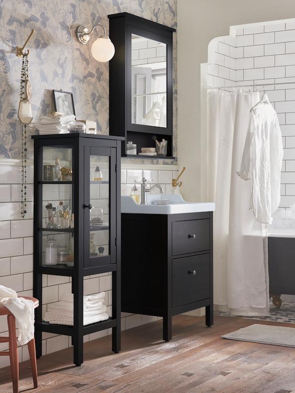 Une salle de bains claire et épurée dans laquelle se trouvent une armoire haute, un meuble pour lavabo et une pharmacie HEMNES noirs.