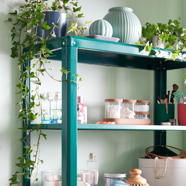 Plants and ornaments on the top shelf of a green KOLBJÖRN shelving unit, with bathroom items below.