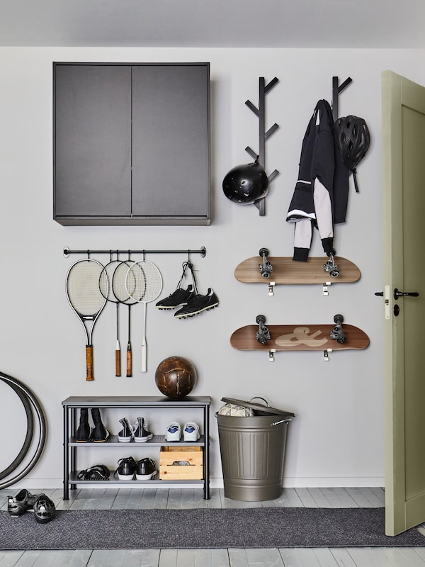A METOD wall cabinet and hooks and a rail holding objects are mounted on a wall above a PINNIG bench with shoe storage.
