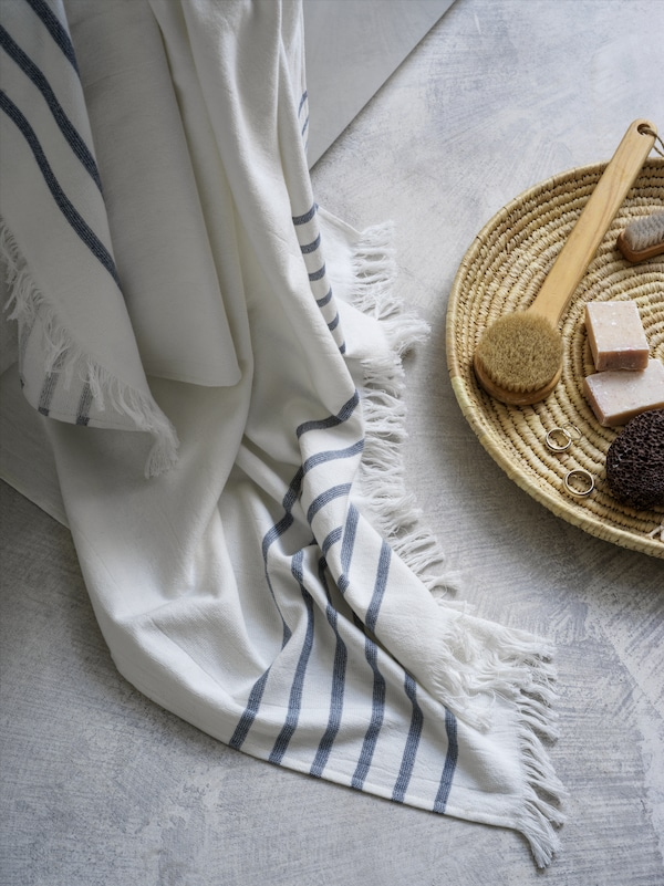 A white/blue striped SIESJÖN bath towel is draped over the side of a bath onto the floor near some brushes, rings and soap.