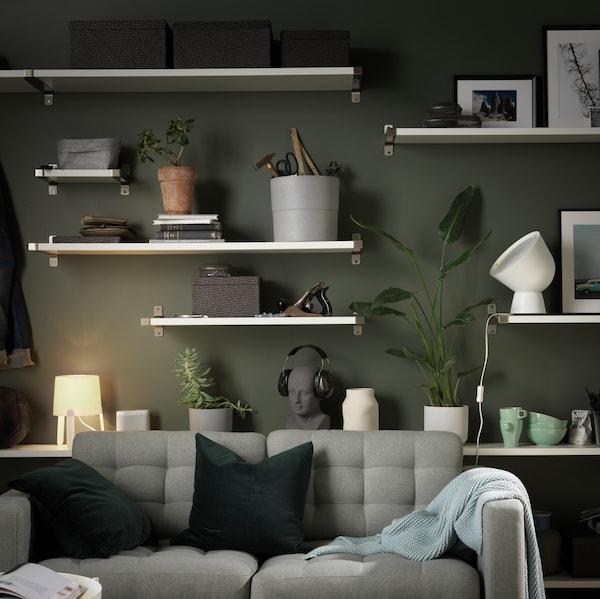 Várias prateleiras BERGSHULT, com vasos, caixas, candeeiros e outros objetos, fixadas a uma parede por trás de um sofá LANDSKRONA.