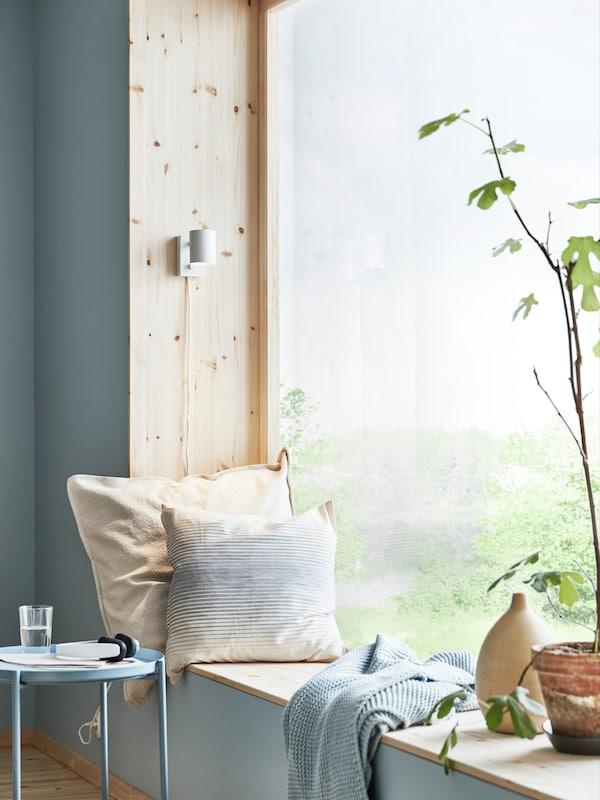 Deux coussins sur un rebord de fenêtre, une table basse et une plante dans un coin lumineux