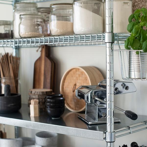 Een metalen voorraadkast met potjes met verschillende ingrediënten en een houder met haken aan de zijkant die een plant vasthoudt.