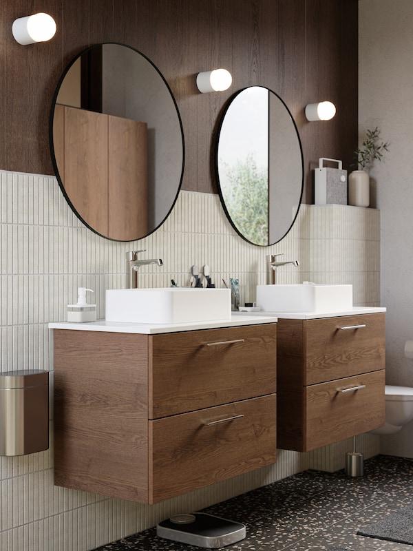 Dua kabinet bawah sink kayu, dua cermin bulat yang besar, tiga lampu dinding terlekap pada dinding, jubin berwarna kuning air, lantai terazo berwarna gelap.