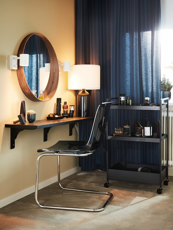 A black NISSAFORS trolley and a blue/chrome chair by a brown-black wall shelf with a round mirror and white wall lamps.