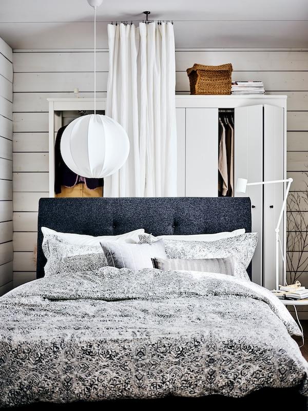 Ein IDANÄS Polsterbett mit der ÄNGSKLOCKA Bettwäsche, einem Beistelltisch und einer weissen DYTÅG Gardine dahinter.