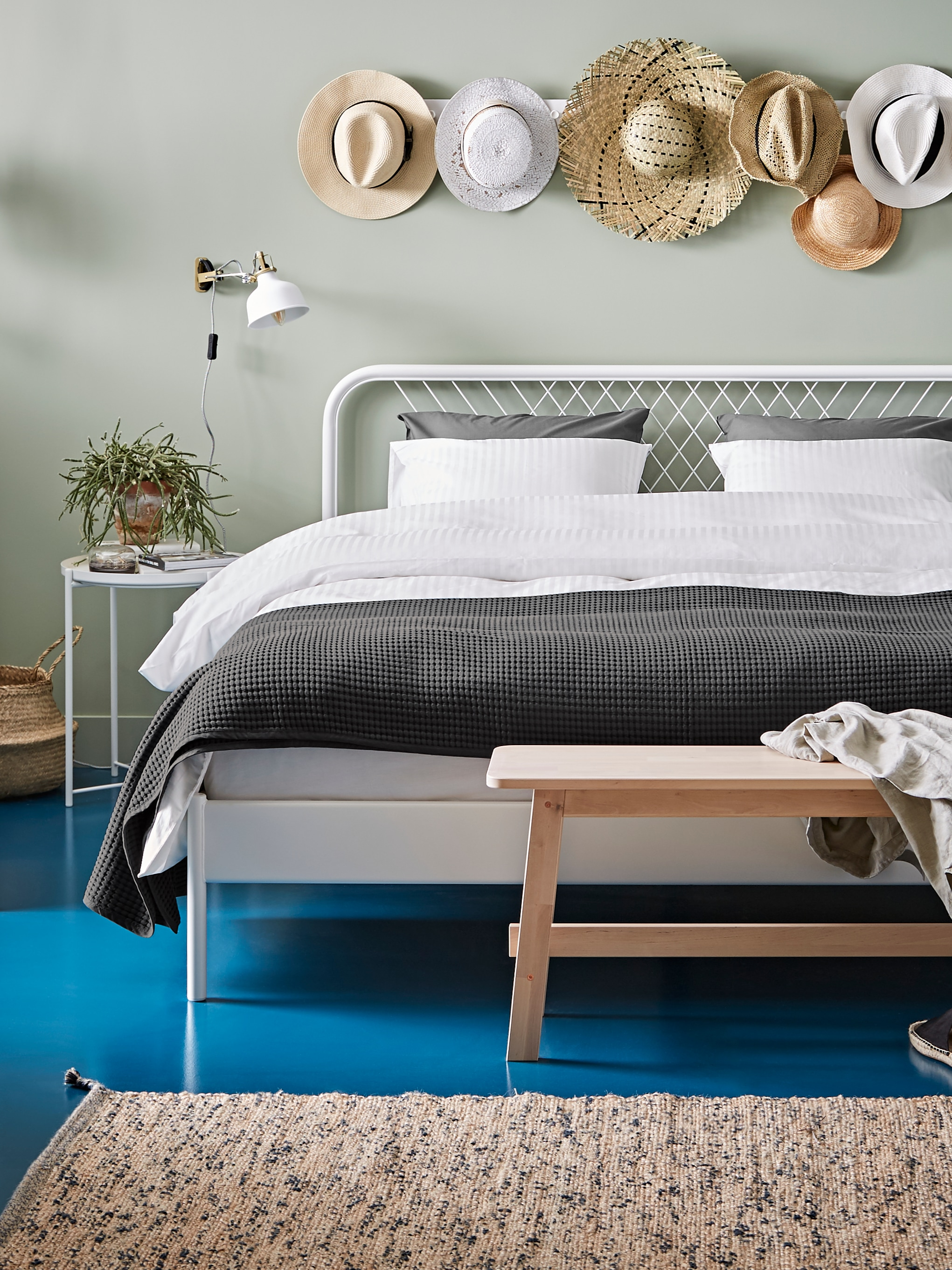 A NESTTUN white bed frame with a white quilt cover and dark grey bedspread on a blue bedroom floor next to white tray tables.