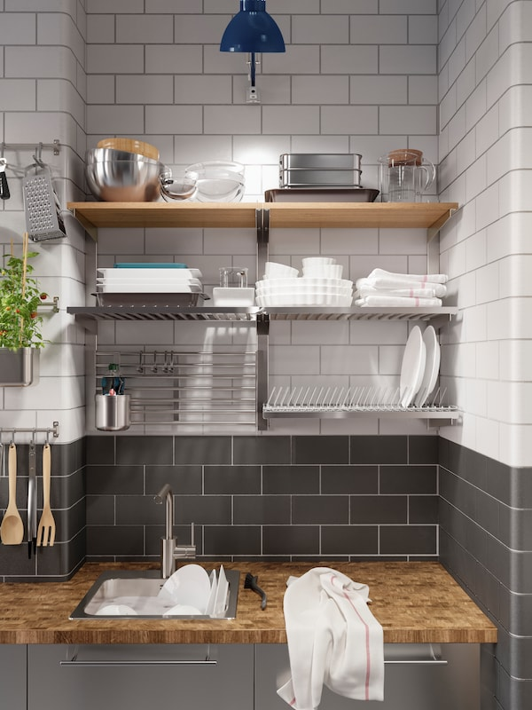 A kitchen in stainless steel with a wooden worktop and a dish drainer. Rails and shelves are mounted on the wall above.