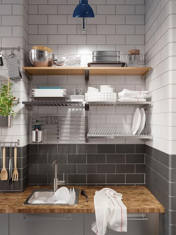 Kuhinja od nerđajućeg čelika s drvenom radnom pločom i oceđivačem suđa. Šine i police su montirane na zid iznad.