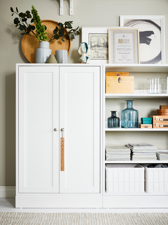 Mobile con zoccolo HAVSTA bianco e scaffale coordinato con vasi, riviste, cestini e decorazioni varie.
