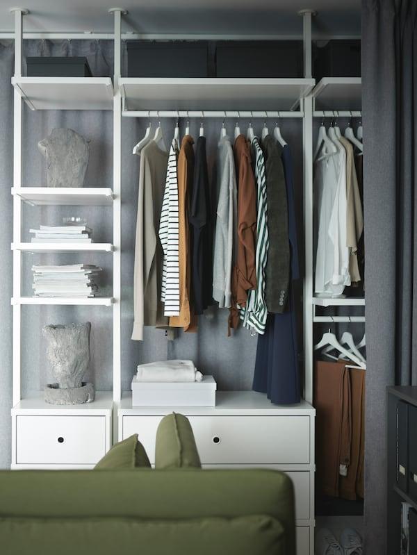 Das ELVARLI Aufbewahrungssystem mit Kleidung, Zeitschriften und Dekogegenständen. Ganz vorne ist eine graue Gardine zu sehen, die es verschliesst.