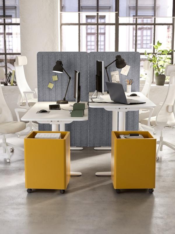 Due scrivanie una di fronte all'altra, cassettiere con rotelle gialle, sedie ergonomiche beige e bianche e lampade da lavoro nere - IKEA