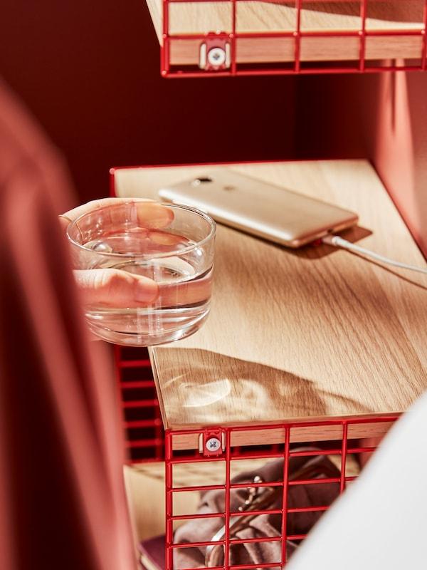 Mâna unei persoane pune un pahar cu apă lângă un telefon inteligent la încărcare pe o etajeră SVENSHULT cu depozitare.