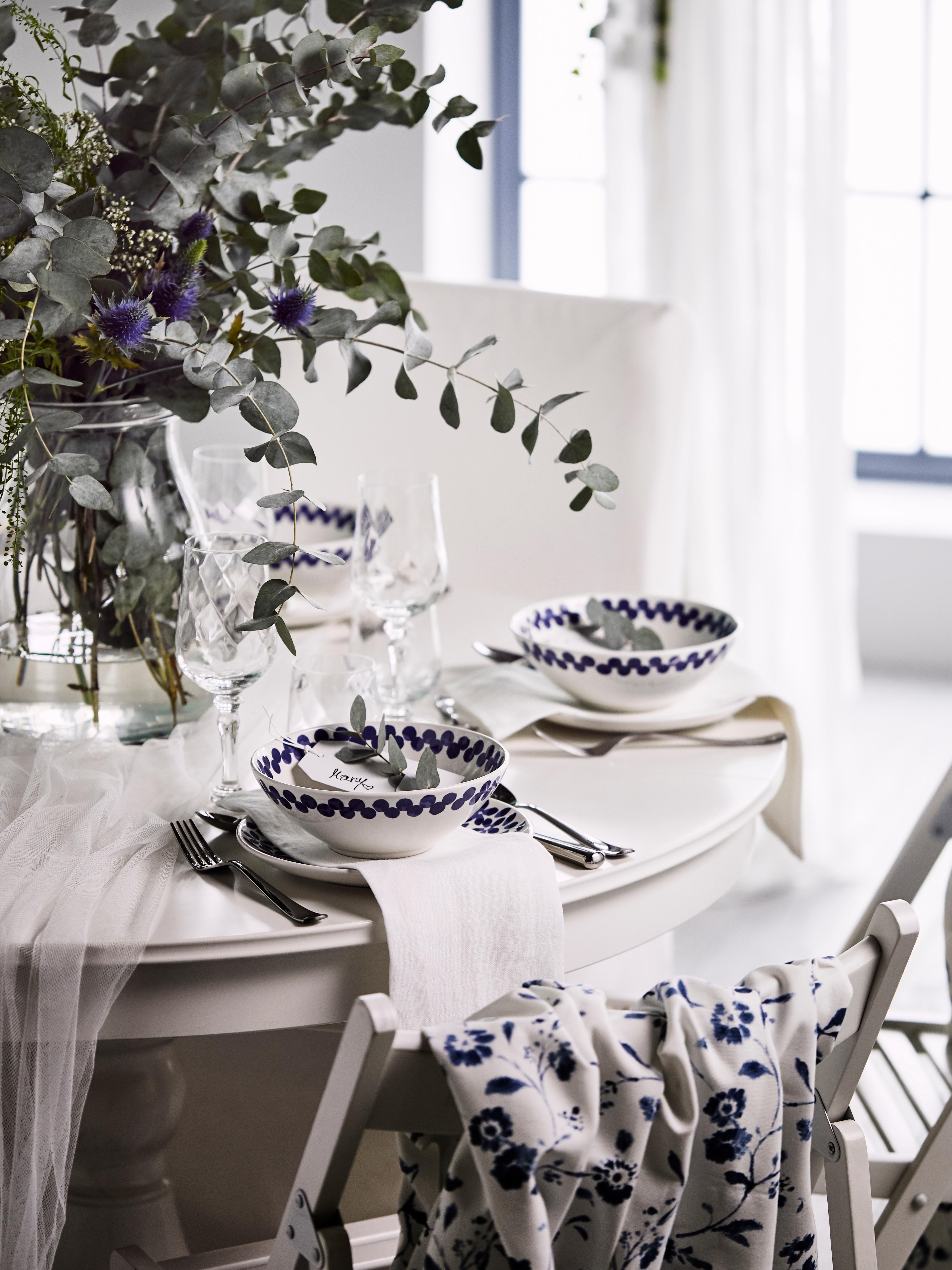 Bols MEDLEM à motifs blancs et bleus sur une table dressée avec des fleurs à côté de chaises pliantes blanches avec du tissu bleu-blanc.
