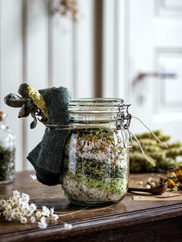 Sklenice KORKEN zčirého skla svíčkem je naplněna domácím potpourri, na hrdle je uvázán tmavě zelený malý ručník HIMLEÅN.